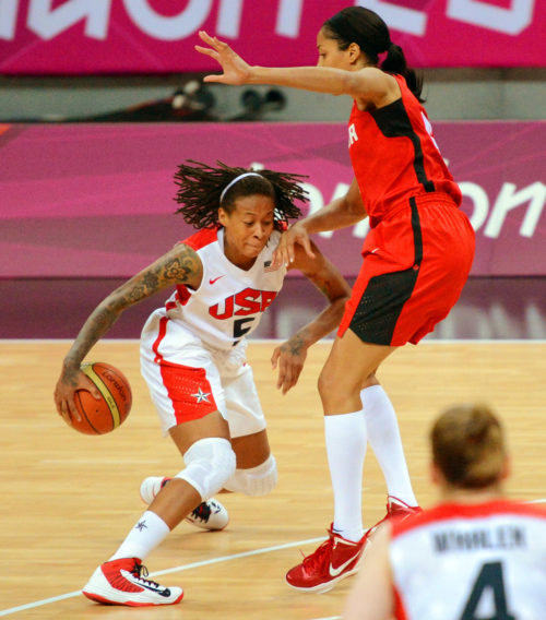 USA Seimone Augustus dribbles past Canada defender in the first quarter of the quarter final game of the women's basketball competition. The USA went on to win 91-48.(AP Photo/Dick Druckman)