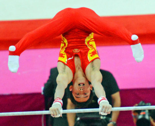 China gymnast, Kai Zou, does a handstand on the horizontal bar in the men's artistic gymnastics final in the North Greenwich Arena. China won the gold medal in the team competition.