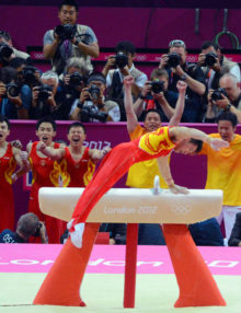China gymnist, C Zhang, finishes a gold medal performance on the pommel horse as his teammates cheer him on. China went on to win the Gold Medal in the team competition in the North Greenwich Arena in the London Olympics.(AP Photo/Dick Druckman)