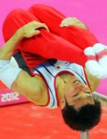 Japan gymnist, Kazuhito Tanaka dismouints from the parallel bars in the men's team competition at the North Greenwich Arena. Japan went on to win the Silver Medal.(AP Photo/Dick Druckman)