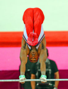 USA gymnist John Orozco, does a headstand on the horizontal bar in the team competition. The USA performed poorly and finished 5th.