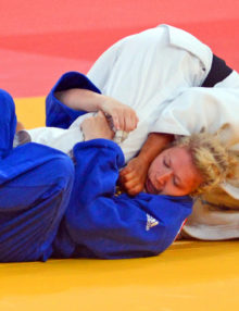 Lucie Decosse(white)from France throws Thiele Kerstin(Blue)from Germany in the women's final judo competition in the London Olympics. Lucie Decosse won the gold medal.(AP Photo/Dick Druckman)