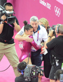 USA gymnist Aly Raisman hugs her coach after completing the vault exercise during the 2012 Summer Olympics in London England. Aly Reisman flips in her floor exercise.