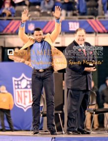 New York Giants Defensive End, MICHAEL STRAHAN, raises his arms to the crowd during the Half time ceremony recognizing his enshrinement into the NFL Pro Football Hall of Fame.