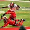 Wisconsin University running back, MELVIN GORDON, leaps over a Rutgers University defender to score a 14yard touchdown in the first quarter giving Wisconsin a 7-0 lead. Wisconsin went on to win 37-0.