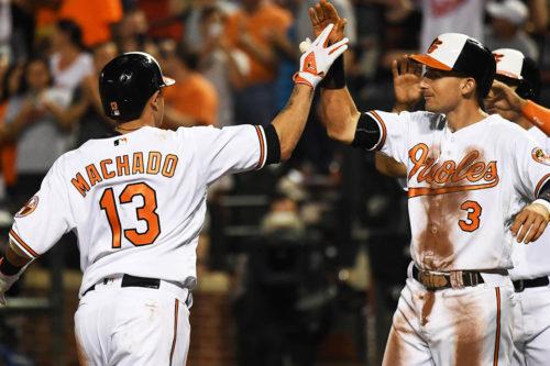 Baltimore Orioles shortstop MANNY MACHADO high fives third baseman RYAN FLAHERTY