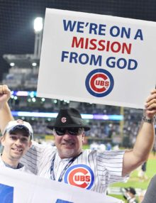 Chicago Cubs fans hold up a sign after game 7 of the World Series suggesting that their was DIVINE influence