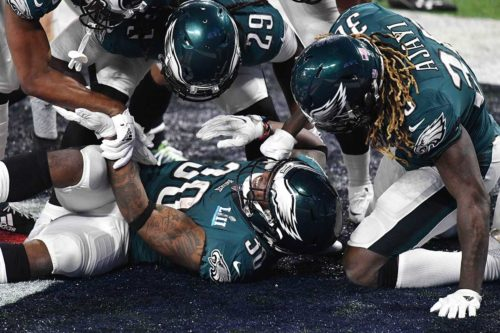 Eagles running back COREY CLEMENT is mobbed by his teammates after scoring