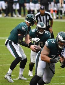 Eagles quarterback Carson Wentz hands off to Wendell Smallwood