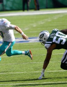 Miami Dolphins quarterback Ryan Tannehill runs a quarterback keeper for a first down