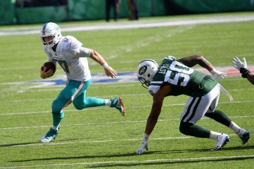 Miami Dolphins quarterback Ryan Tannehill runs a quarterback keeper for a first down